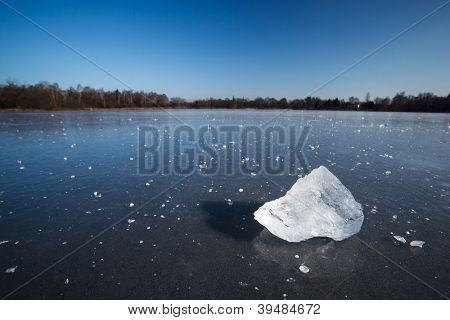 Freezing winter temperatures: block of ice lying on the surface of a frozen pond on a sunny winter day
