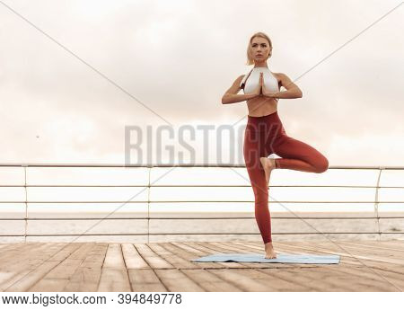Yoga Practice At Sunrise. Young Woman Yogi Stands In Pose With Namaste On The Beach In The Morning