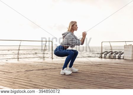 Healthy Woman Training On Seaside Promenade. Sportswoman In Sportwear Doing Squat Exercise On The Be