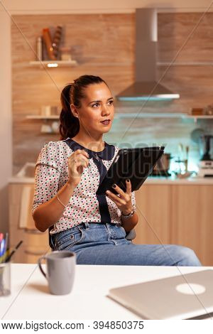 Thoughtful Freelance Woman Using Tablet Pc While Working Overtime In Home Kitchen. Using Modern Tech