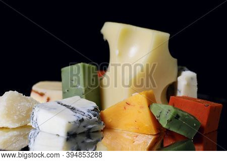 Pieces Of Assorted Cheese Cheeses On A Black Background. Reflection Of Pieces Of Cheese Of Different