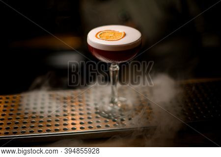 Wine Glass Of Drink With Foam And Slice Of Citrus Stands On Smoky Bar Counter.