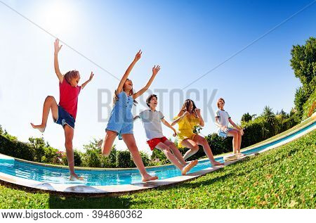 View From Bellow Of Group Of Happy Teen Children In Mid Air Fall Into Pool Water Hands Up Laughing A
