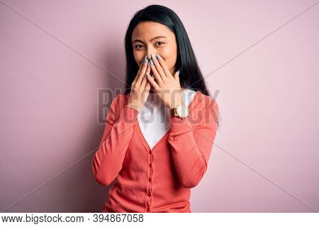 Young beautiful chinese woman wearing casual sweater over isolated pink background laughing and embarrassed giggle covering mouth with hands, gossip and scandal concept