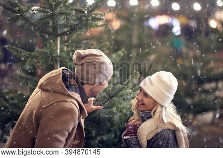 A young cheerful couple enjoying buying a christmas tree in a magical night of a snowy weather in the city. Christmas tree, love, relationship, Xmas, snow