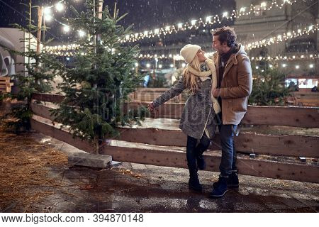 A young couple in love enjoying beautiful christmas festival in a magical night of a snowy weather in the city. Christmas tree, love, relationship, Xmas, snow