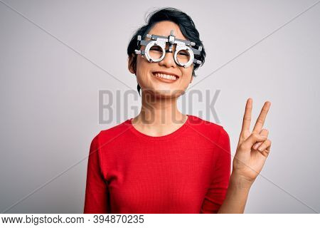 Young beautiful asian girl wearing optometry glasses standing over isolated white background smiling with happy face winking at the camera doing victory sign. Number two.