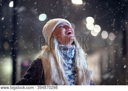 Portrait of a woman walking outside on a winter night; Winter joy concept