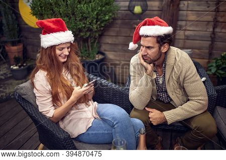 angry  caucasian guy looking at  female texting  on her cell phone on new year party. rude behavior concept