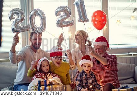 Happy family looking forward presents at New Year eve in festive home atmosphere. New Year, holiday, family time together