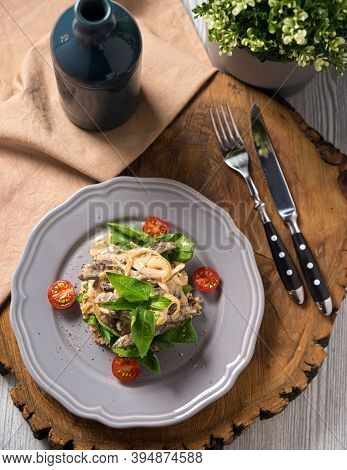 Beef Stroganoff Cooked In A Creamy Sauce, With Quinoa, Cherry Tomatoes, Basil Leaves On A Gray Ceram