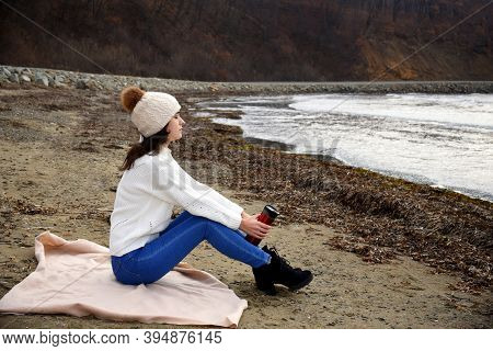 Young Woman In White Sweater, Hat With Pom-pom, Sitting On The Shore Of The Japanese Sea With Closed