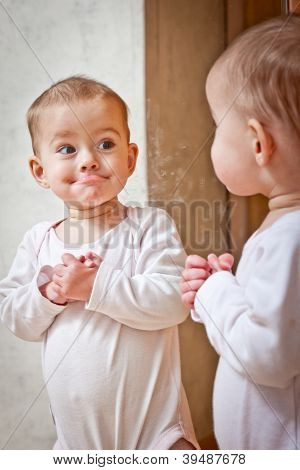 Baby standing against the mirror