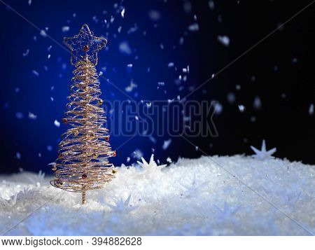 Golden Christmas tree ornament artistic still life on dark blue background with snow