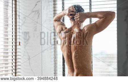 Unrecognizable Young Muscular Man Taking Shower Standing Back To Camera Washing Body Under Falling H