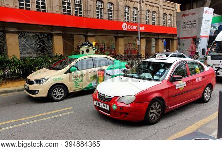 Kuala Lumpur, Malaysia - March 12, 2019: Decorated Grab Taxi And Traditional Red Taxi Standing On St