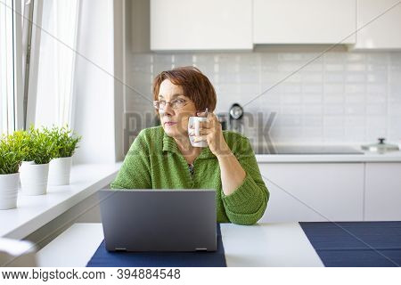 Thoughtful Senior Woman With A Cup Of Warm Tea Working From Home Using Laptop. She Looking Away.