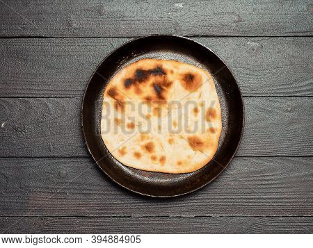 Fresh Naan Bread In Cast-iron Pan On Dark Wooden Background With Copy Space. Top View Of Perfect Naa