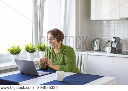 An Elderly Woman Makes An Online Video Call Using A Laptop. She Smiles And Enjoys Meeting Her Online
