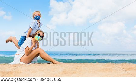 Mother, Child In Masks Have Fun On Sea Beach. New Rules To Wear Cloth Face Covering At Public Places