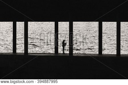 Silhouette Of Fisherman With Fishing Rod On Pier. Lonely Old Fisherman On Sea Background. Black And