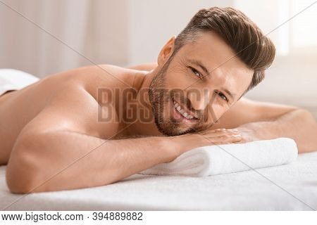 Happy Middle Aged Man Attending Spa Salon On Weekend, Lying On His Belly On Massage Table, Closeup.