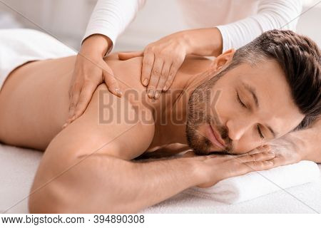 Closeup Of Handsome Man Having Full Body Massage At Male Spa. Unrecognizable Female Therapist Rubbin