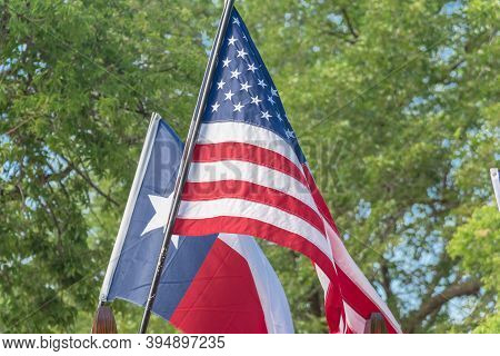 Proudly Texas And American Flags Flying And Green Trees Background At A Rally Near Dallas, Texas, Us