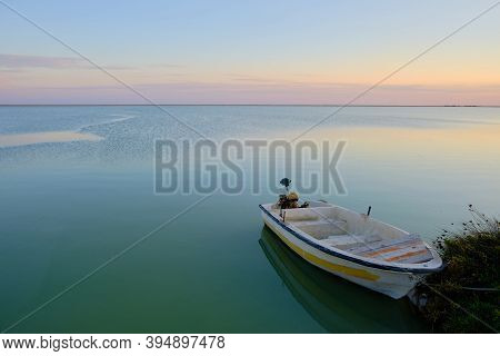 Boat With An Electric Motor Is Moored To The Shore. Seaside Sunset With Boat