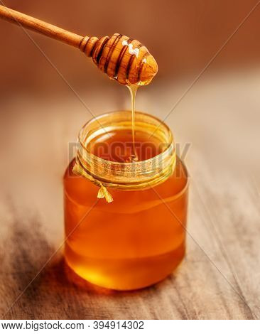 Honey With Wooden Honey Dipper On Wooden Table. Copyspace.