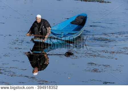 Kashmir, Jammu, India - January 7, 2021 : Old Man Rowing Boat With His Reflection On The Surface Wat