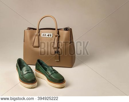 A Pair Of Green Women's Shoes With Thick Soles. Nearby Is A Light-colored Women's Leather Bag. Side