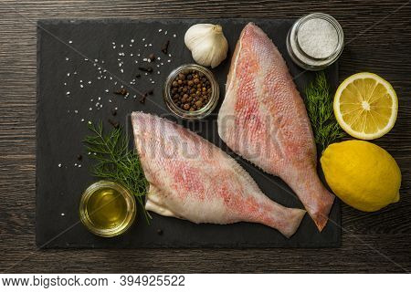 Sea Perch On A Black Board. Sea ??bass On A Black Board With The Ingredients For It Cooking. Fish On