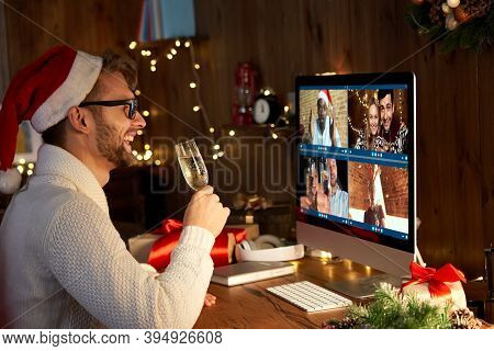 Happy Young Man Wearing Santa Hat Drinking Champagne Talking To Friends On Virtual Video Call Meetin