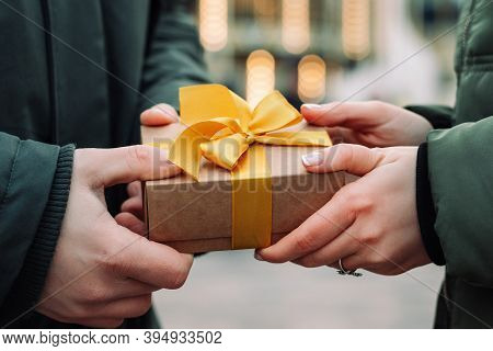 Hands Of A Couple With A Gift Present. Man Gives A Small Present With A Yellow Ribbon To His Girlfri