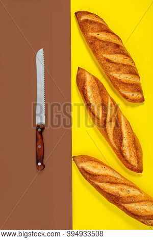 Freshly Baked Traditional Baguettes And A Bread Knife On A Contrasting Two-color Background With A C