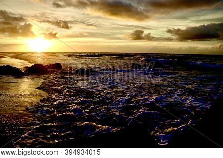 Sunrise Over The Atlantic Ocean Shining Bright Against The Gleaming Sand