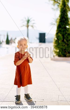 An Adorable 2-year Old Is Eating A Sweet Roll In The Park By The Sea