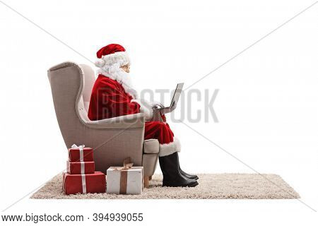 Santa claus working on a laptop and sitting in an armchair with presents on the floor isolated on white background