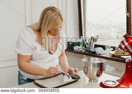 А Young Woman Is Putting The Freshly Whipped Meringue On A Tray With A Spoon In The Kitchen. A Girl