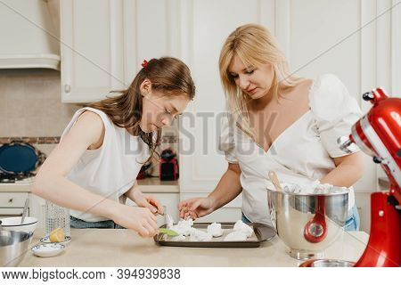Two Young Women Are Putting Diligently The Whipped Meringue On A Tray With A Spoon And A Scapula In