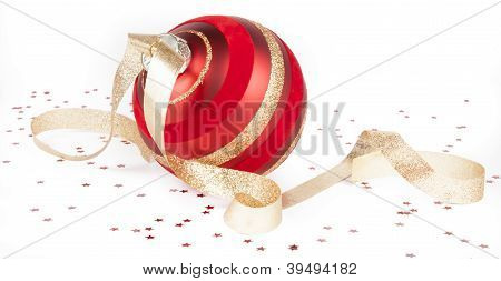 Christmas ornament with gold ribbon and confetti on white