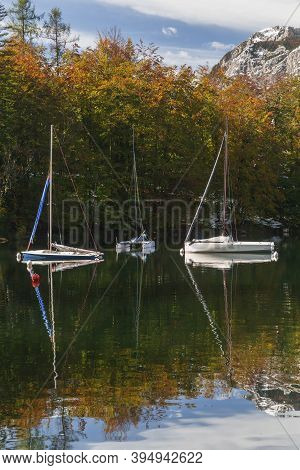 Three Yachts On Lake Bohinj In Slovenia. Alps And Autumn Forest