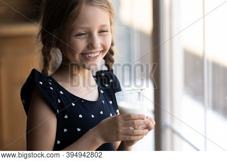 Naughty Little Girl Standing By Window Drinking Dairy From Glass