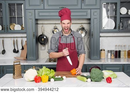 Guy With Angry Face In Red Chef Hat And Apron With Knife Cut Vegetables On Table In Kitchen. Cooking