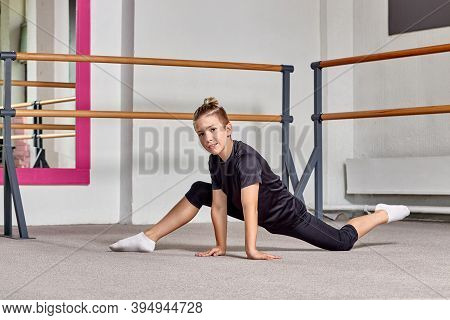A Young Guy Looks At The Camera And Tries To Sit On The Splits. Ballet School.