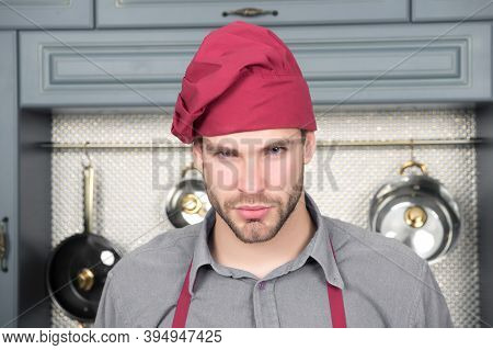 Cook Man With Beard On Serious Face In Kitchen. Chef In Red Hat, Apron On Blue Shirt. Food Preparati