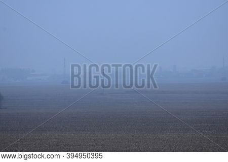 Vast And Fertile Fields From Which Corn Was Harvested. Fog And Village In The Background