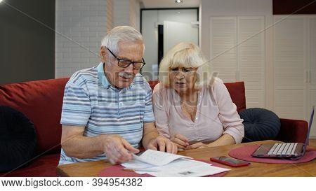 Stressed Senior Couple Discuss Unpaid Bank Debt Holding Bills, Doing Paperwork, Planning Budget, Dis
