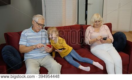 Senior Couple Grandparents With Child Girl Grandchildren Spending Time Home Together, Sitting On Sof